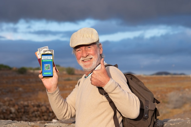 Attractive senior man hold mobile phone and shows health passport app for people vaccinated against coronavirus