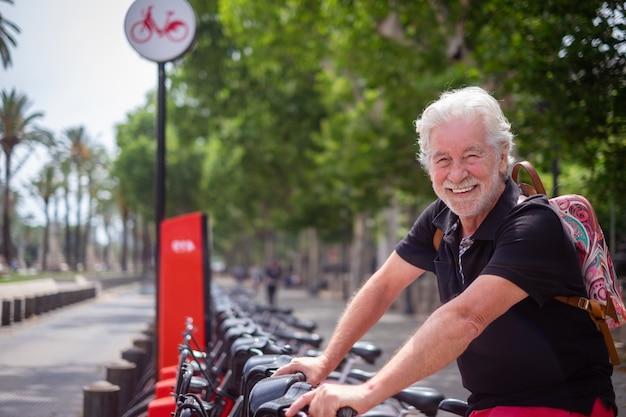 매력적인 노인은 공공 공원에서 전기 자전거를 빌리며 행복하게 웃고 있습니다. 자유와 건강한 라이프 스타일을 즐기는 카메라를보고 수염 난 백인