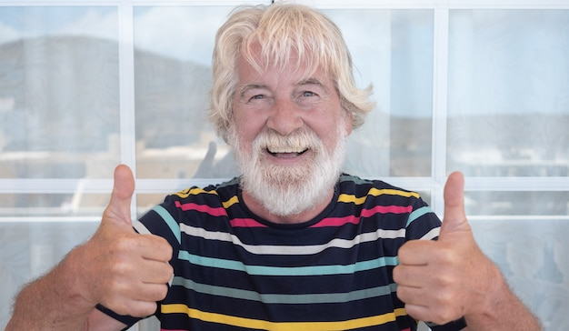 Attractive senior man white beard and hair gesturing ok with hands outdoor on the terrace. funny expression. striped t-shirt colorful