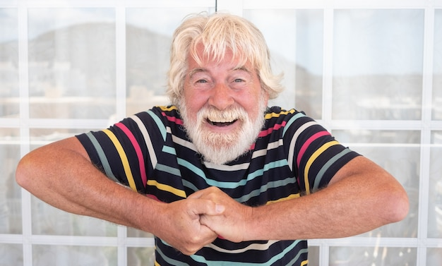 Attractive senior man white beard and hair gesturing  with hands outdoor on the terrace. funny expression. striped t-shirt colorful