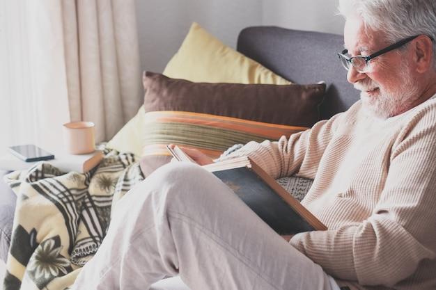 魅力的な年配の男性、白い髪と眼鏡、古い本を読んで自宅のソファに座っています。退職者のためのリラックスしたライフスタイル