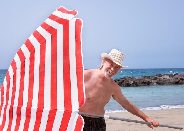 수염과 모자가 우산을 들고 해변에 서 있는 매력적인 노인 - 물 위의 수평선