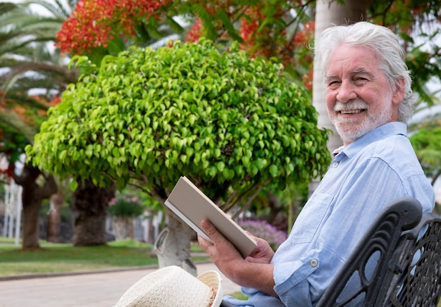 Attractive senior man with white beard smiles sitting in the park reading a book