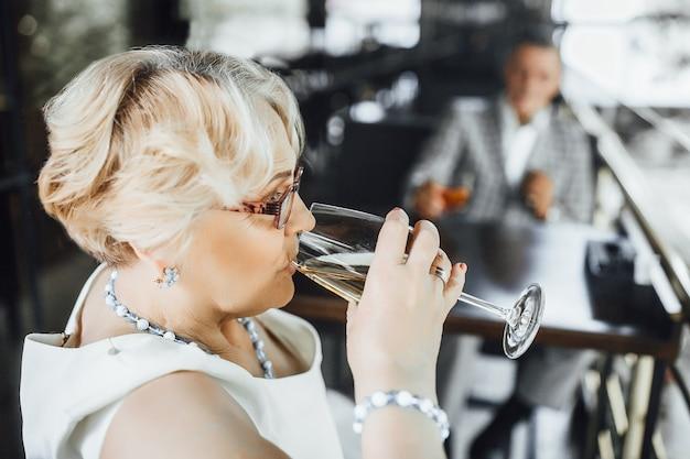 魅力的な年配の女性は、サマーテラスで白ワインを楽しんでいます。