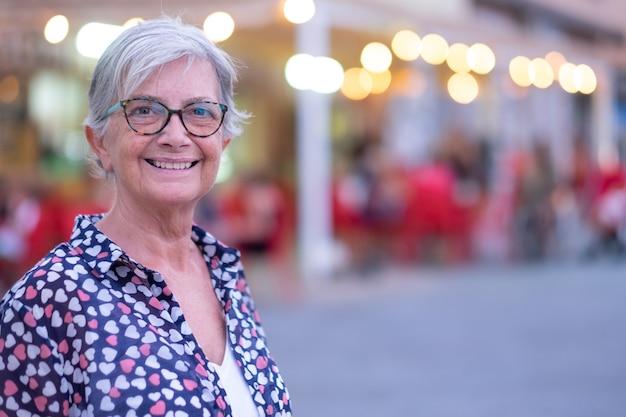 カメラを見て、日没の光で街の屋外で魅力的な年配の女性。自由と休日を楽しむ白人の白い髪