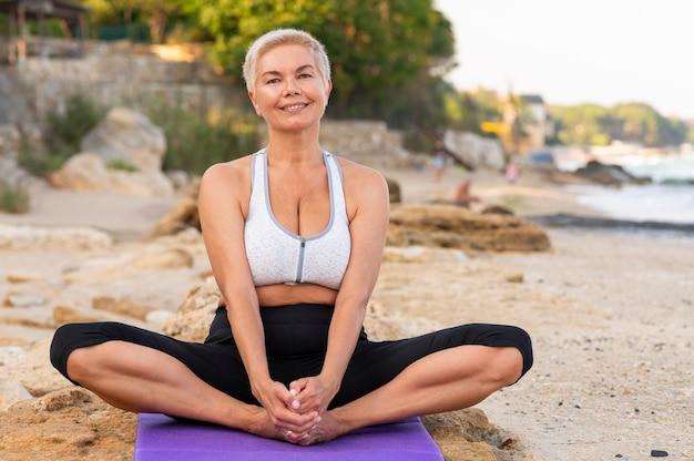 매력적인 수석 여자가 해변에서 요가 위치에 다리를 꼬고 앉아있다