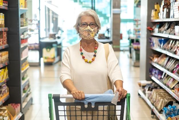 매력적인 노인 여성은 보호용 안면 마스크를 쓰고 카트를 밀고 슈퍼마켓에서 물건을 산다