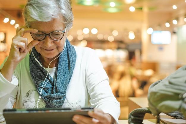 탑승을 기다리는 동안 디지털 태블릿에서 소셜 미디어를 사용하여 공항 카페에 앉아 있는 매력적인 노인 여성. 휴가에 행복한 성숙한 여행자