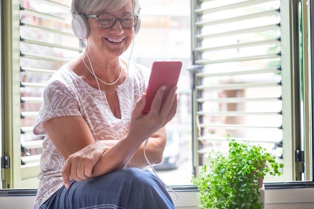 헤드폰을 끼고 휴대폰을 사용하여 창 가까이에 앉아 있는 매력적인 고위 여성. 은퇴 생활을 즐기는 웃는 백인 여성