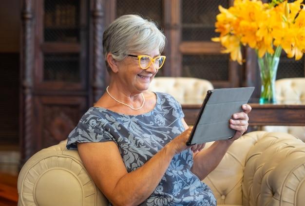 디지털 태블릿을 사용하여 소파에 앉아 매력적인 고위 여자. 편안한 순간을 즐기는 웃는 현대 퇴직자