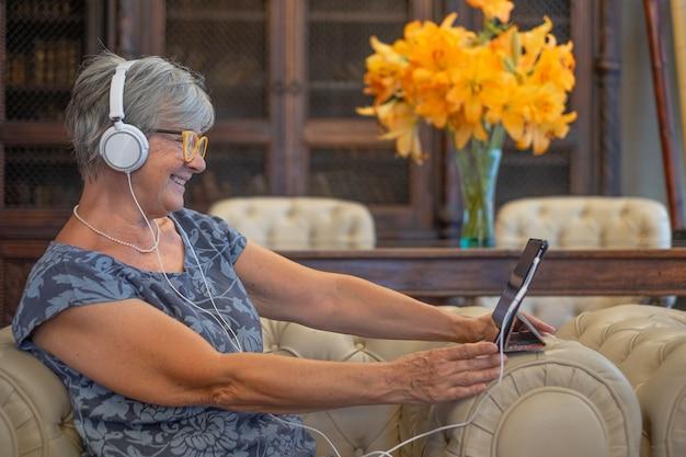 헤드폰을 끼고 소파에 앉아 디지털 태블릿으로 화상 통화를 하는 매력적인 고위 여성. 편안한 순간을 즐기는 웃는 현대 퇴직자