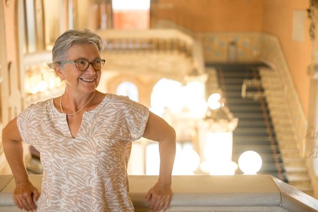 바르셀로나의 유서 깊은 궁전을 방문하는 매력적인 고위 여성, 계단에 서서 웃고