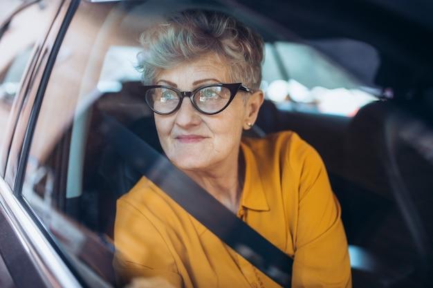 Привлекательная старшая женщина в очках, сидя в машине. выстрелил сквозь стекло.
