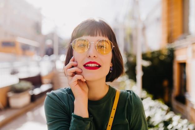 노란색 선글라스 epxressing 관심에 매력적인 관능적 인 여자. 봄 날에 편안한 아름 다운 백인 여자입니다.