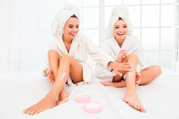 バスローブを着た魅力的な官能的な女性が脚にクリームを塗る