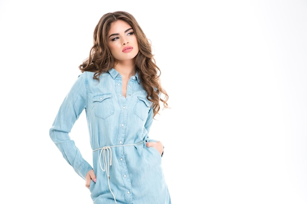 Привлекательная чувственная молодая женщина с красивыми длинными вьющимися волосами, стоящая и думая над белой стеной
