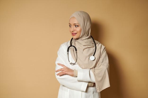 魅力的な穏やかなイスラム教徒の医師、ヒジャーブの首に聴診器を持ち、腕を組んで立って、コピースペースのあるベージュの表面を横に見ています