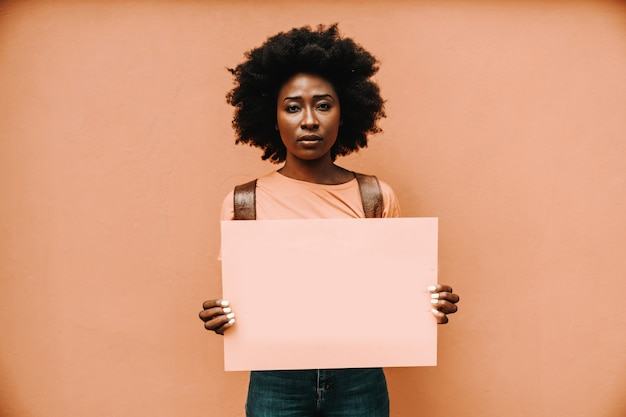 Attractive serious african woman standing and holding blank paper.