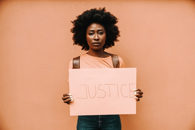 Attractive serious african woman standing and holding paper with justice title.