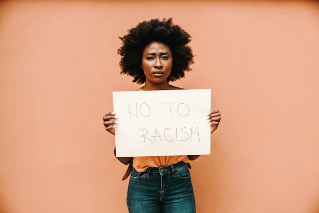 Attractive serious african woman standing and holding paper with no to racism title.