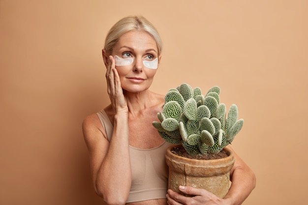 Attractive serious blonde aged woman with blonde hair touches face applies beauty patches under eyes embraces pot of cactus