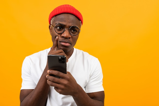 Attractive serious charming black man in a white t-shirt with a smartphone in his hands on a yellow