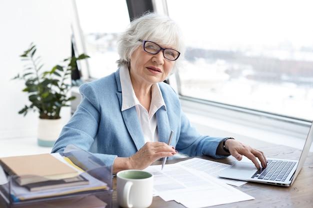 ラップトップを持ってオフィスに座って、机の上にキーボードと署名の書類を持って、自信を持って見ている成熟した年齢の魅力的な真面目な女性最高経営責任者。人、高齢化、仕事、キャリアの概念