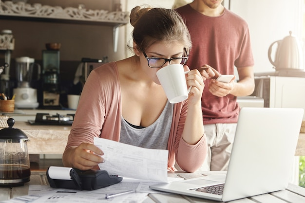 Attractive serious female in spectacles drinking coffee and studying document in her hands, managing family budget and doing paperwork at kitchen table with pile of bills, laptop and calculator