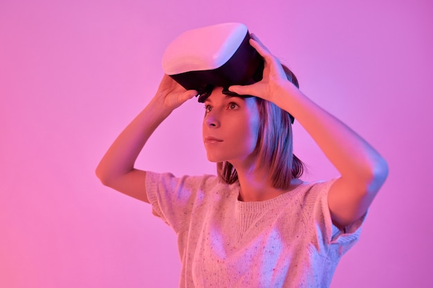 Attractive serious focused woman in casual wear using virtual reality glasses isolated on neon pink