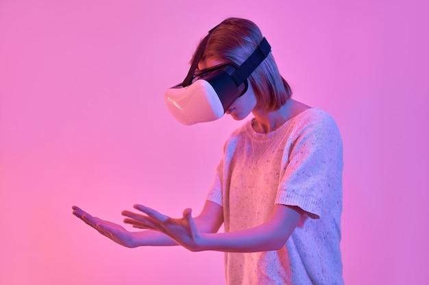 가상 현실 안경을 사용하는 캐주얼 옷에 매력적인 심각한 집중된 여자는 네온 핑크에 고립 된 그녀의 손을 본다
