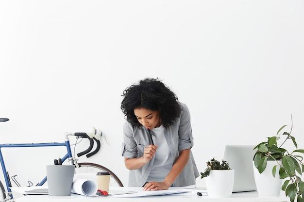 Attraente giovane ingegnere donna di razza mista serio e concentrato con i capelli ricci tenendo la penna
