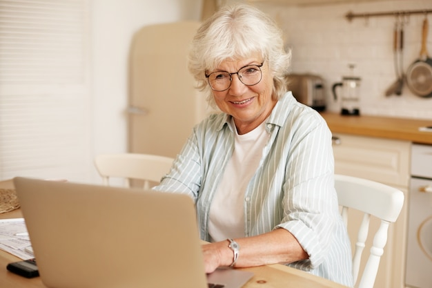 Attractive serious self employed woman pensioner working distantly from home, sitting in kitchen in front of open portable computer, wearing eyeglasses. people, age, job and occupation concept