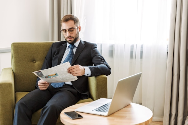 Attractive serious young businessman wearing suit sitting in a chair at the hotel room, reading newspaper