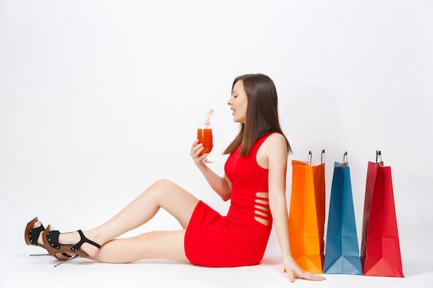 飲み物のカクテル、白い背景で隔離の買い物の後の購入でマルチカラーのパケットと一緒に座っている赤いドレスの魅力的なセクシーな魅力の若い女性。広告用のスペースをコピーします。