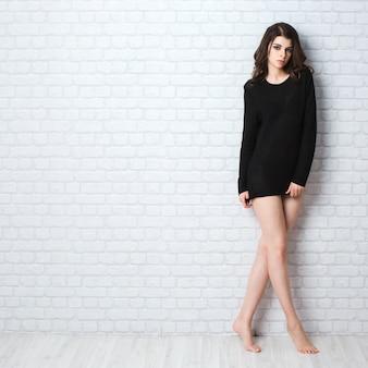 Attractive sexy woman in black posing indoor.