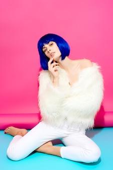 파란 가발과 분홍색과 분홍색 파란색 배경에 흰색 모피 코트에 매력적인 섹시한 여자