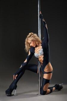 Привлекательная сексуальная женщина-танцор полюса, выступающая на сером фоне