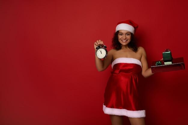 산타 카니발 의상을 입은 매력적인 섹시한 젊은 혼혈 여성은 카메라에 알람 시계와 크리스마스 선물 상자를 보여주고, 광고를 위한 복사 공간이 있는 빨간색 배경에 포즈를 취한 귀여운 미소를 보여줍니다.