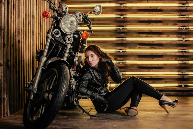 Attractive sexy young woman in black leather jacket and leather jeans were sitting next to the bike on wooden wall background in studio image horizontally