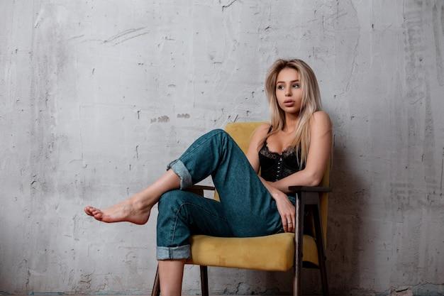 빈티지 의자에 포즈를 취하는 세련된 청바지에 검은 레이스 보루에 자연스러운 메이크업과 금발 머리를 가진 매력적인 섹시한 젊은 여자