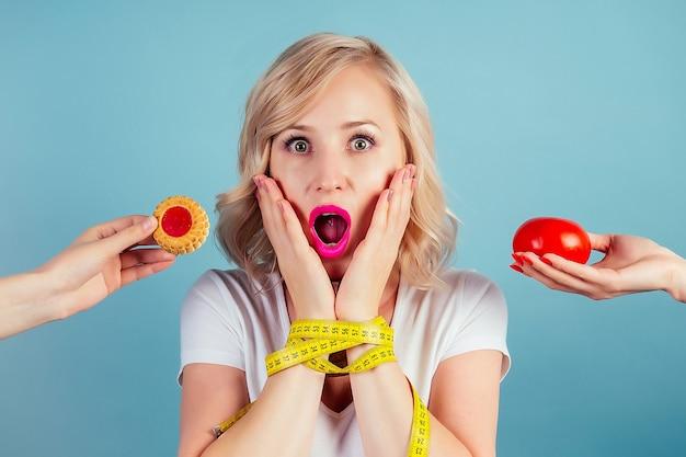 Привлекательная шокированная и пораженная блондинка делает выбор между высококалорийным печеньем и помидорами с рулеткой в студии на синем фоне. концепция здорового питания