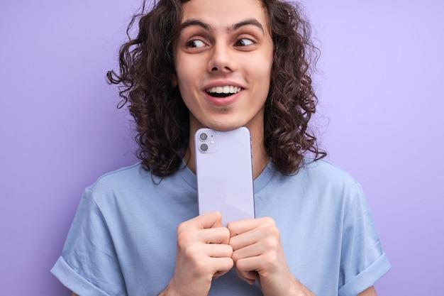 電話を持っている魅力的なショックを受けた男は、maの衝撃的な肖像画でソーシャルネットワークの信じられないほどのニュースを読みます...