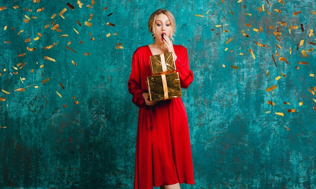 Attractive shocked woman in stylish red dress celebrating christmas and new year with gifts