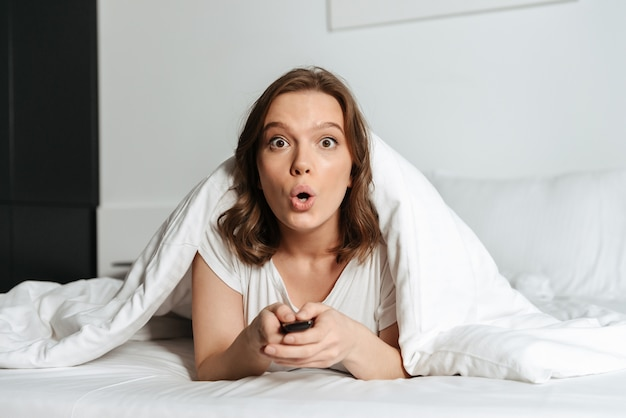 Attractive shocked young woman lying in bed at home watching tv