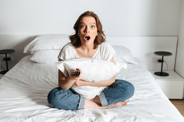 Attractive shocked young woman sitting on bed at home watching tv