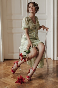 Attractive short-haired beautiful woman in floral dress looks away, sits on transparent chair and holds red flowers