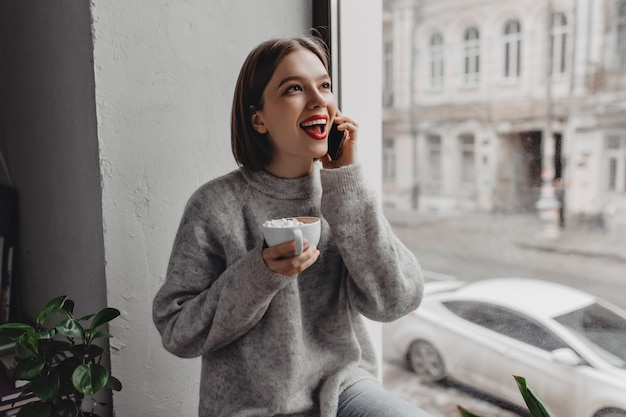 Attractive short-haired girl with red lipstick dressed in gray sweater talking on phone and holding cup of cocoa with marshmallows against window.