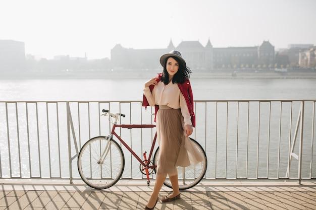 Attraente donna dai capelli corti in piedi sull'argine con la bicicletta