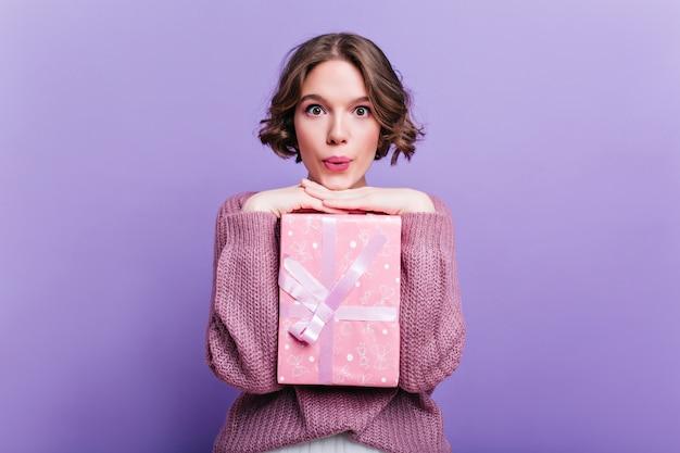 紫色の壁に驚いた表情でポーズをとるプレゼントボックスを持つ魅力的な短髪の女性。リボンで飾られた大きな贈り物を保持しているブルネットの髪を持つ魅力的な女の子の屋内写真。