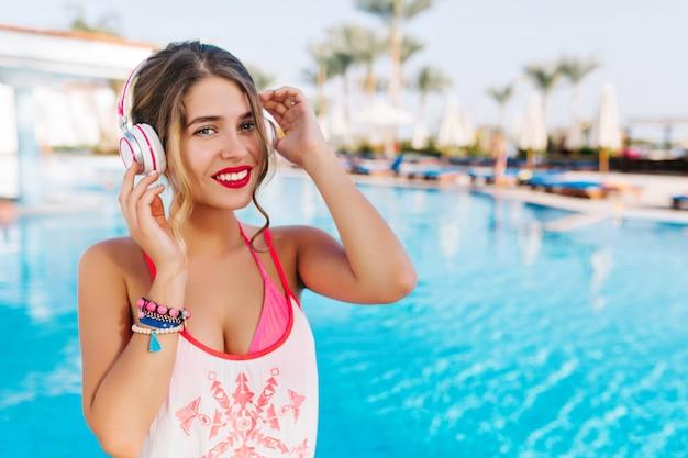 Attraente ragazza timida in costume da bagno rosa e canotta bianca ascoltando musica in cuffia vicino alla piscina all'aperto, in attesa di amici